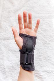 手首サポーターをした女性の手
