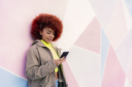 beautiful woman with afro hair looking at her smartphone