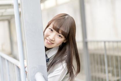 学校の外廊下でほほ笑む女子高生