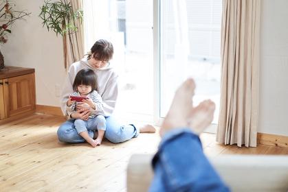 ソファで寛ぐアジア人のお父さんと動画を見る母子