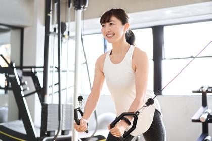 トレーニングジムでケーブルマシンを使うアジア人女性