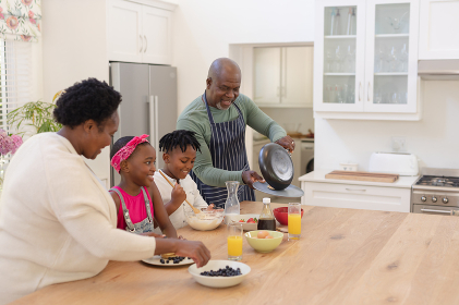 African american grandparents cooking with smiling grandson and granddaughter in kitchen. family spending quality time together.