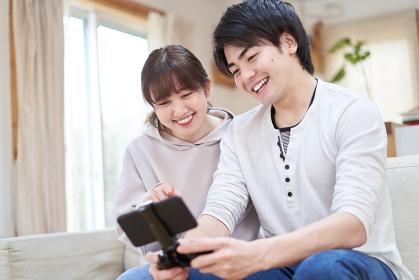 スマートフォンでゲームをするアジア人カップル