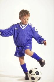 Portrait, Ganzfigur, Junge mit kurzen Haaren, Fussballer, 8 Jahre, bekleidet mit blauem Trikot und Stutzen beim Tribbeln mit dem Ball