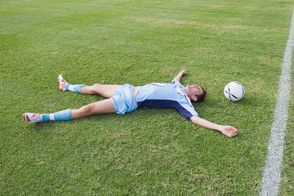 芝の上に大の字になるサッカー選手とボール