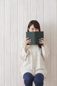 本で顔を隠した日本人女性