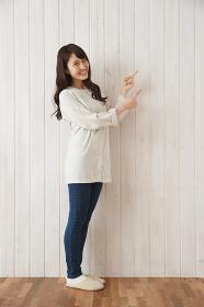 両手の人差し指を指す日本人女性