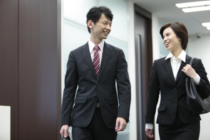 歩くビジネスマンとビジネスウーマン