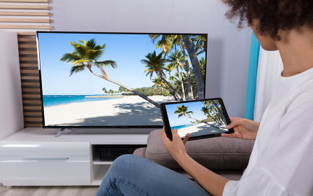 Woman Connecting TV Through Wi-fi On Digital Tablet
