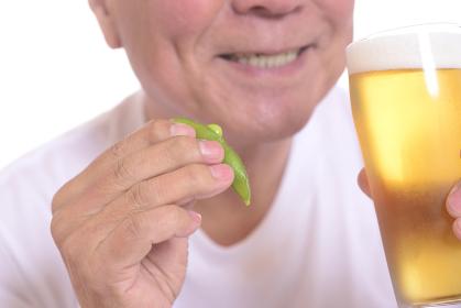 枝豆を食べながら笑顔でビールを飲むシニア