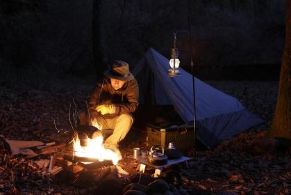ソロキャンプ 焚火をする男性