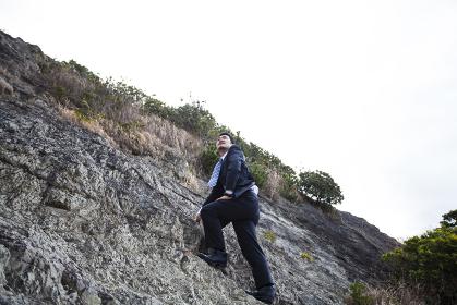 崖を登るビジネスマン
