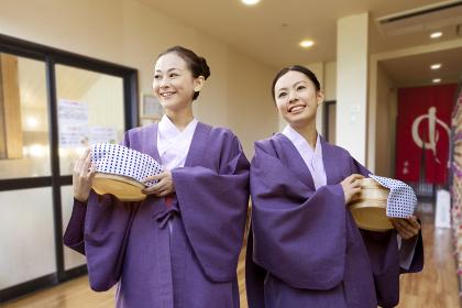 風呂桶を持った浴衣姿の女性二人