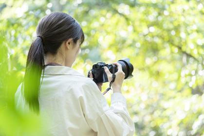 自然の中でカメラを構える若い女性
