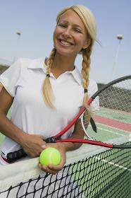 Female Tennis Player at net on tennis court portrait