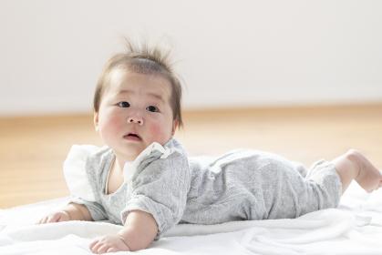明るい部屋の中でうつ伏せの乳児