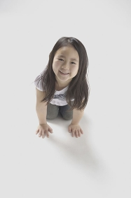 立ち膝で床に手をつき微笑む6歳の女の子