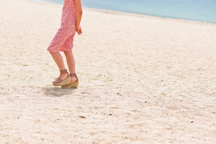 砂浜を歩く女性の足元