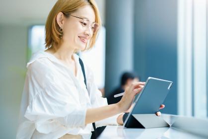 街なかでタブレットPCを操作する女性