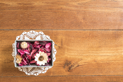 a basket with dried flowers on the wooden floor