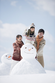 雪だるまの側で微笑む家族