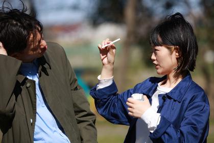 女性にタバコを取り上げられる男性
