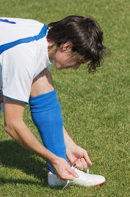 スパイクの紐を絞めるサッカー選手
