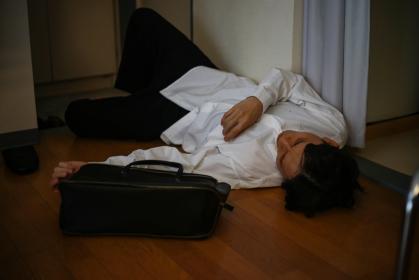 飲みすぎて玄関で寝る男性