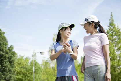運動中にスマートフォンを片手に会話をする親子