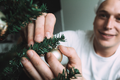 Male wearing white t-shirt decorating a Christmas tree in summer