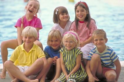 Portrait, Gruppe von 7 lachenden Kindern im Alter von 6-8 Jahren bekleidet mit bunter Sommerkleidung vor dem glitzernden Wasser eines Schwimmbeckens