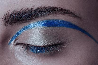 Beautiful macro shot of female eye make-up. Blue eye. Creative make-up. Perfect shape blue line make-up and long lashes and bushy eyebrows. Cosmetics. Beautiful eyes make-up. Close-up