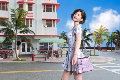 リゾート地の施設の前の道に白いかわいいワンピースを着てピンクのショルダーバッグを持った20代の女の子