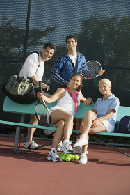 Four mixed doubles tennis players at bench at tennis court portrait