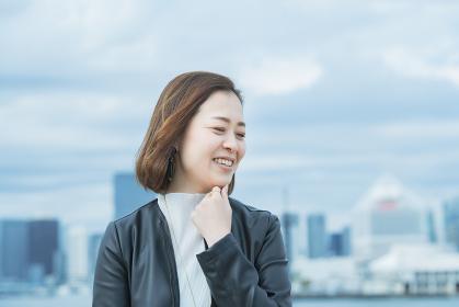 屋外で笑顔を見せるオフィスカジュアルスタイルの女性