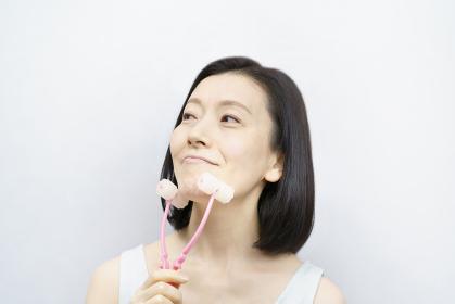 小顔マッサージをする中年女性