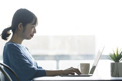 テーブルの上でノートPCを操作する女性