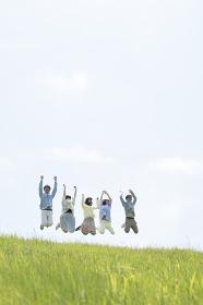 草原でジャンプをする大学生