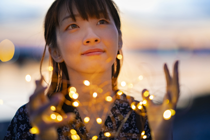 イルミネーションライトを両手で包む若い女性