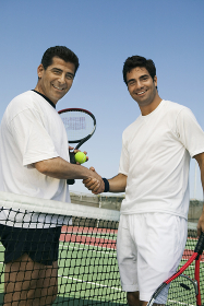 Tennis Players shaking hands over net on court portrait
