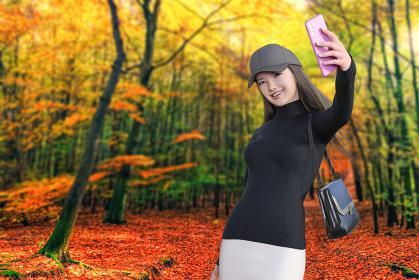 綺麗に色づく紅葉した森を散歩する笑顔の女の子がピンクのスマートフォンで自然を背景に自撮りをする