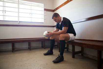 Serious player with rugby ball sitting in room