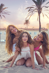 Best friends teen girls having fun on a beach sand at sunset filtered image