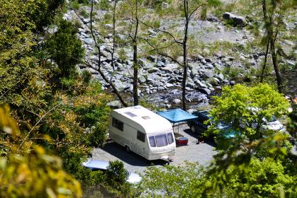 キャンピングカーで河原でアウトドアキャンプを満喫する休暇