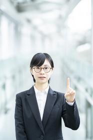 人差し指を立てるポーズをするスーツ姿の若い女性