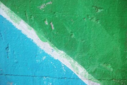 斜めの白い線で青色と緑色を分けたペイントの古いコンクリートの壁