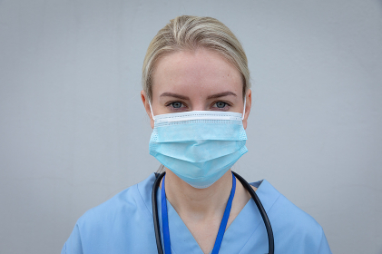 Portrait of Caucasian female medical professional with stethoscope around neck, wearing face mask looking at camera. Social distancing and hygiene in workplace during Coronavirus Covid 19 pandemic.
