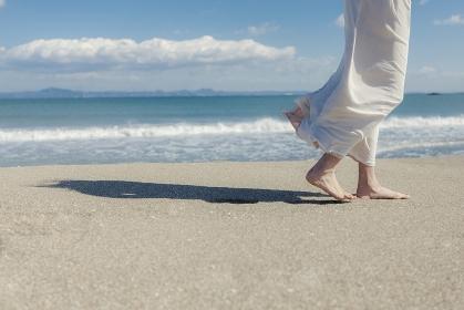 砂浜を歩く日本人女性の足元