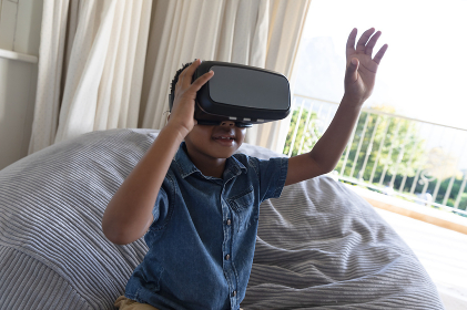 Happy african american boy using vr headset and smiling at home. childhood with technology, spending free time at home.