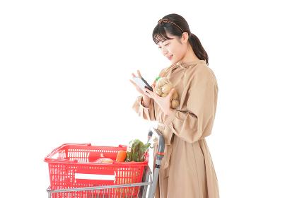 スーパーで食品の原産地を調べる若い女性